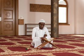 stock photo of islamic religious holy book  - Black African Muslim Man Reading Holy Islamic Book Koran [[** Note: Shallow depth of field ** Note: Visible grain at 100%, best at smaller sizes - JPG