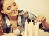 picture of enthusiastic  - Woman assembling wooden furniture using screwdriver - JPG