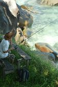 pic of fishing rod  - elderly man fishing in the sea with a fishing rod - JPG