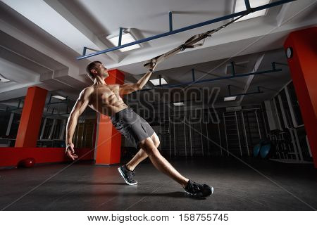 poster of Fitness man workout on the rings. Fitness man in the gym. Fitness style. Workout on rings. Sport and fitness