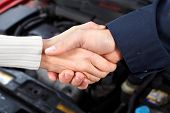 Handshake. Mechanic and client woman in auto repair shop.