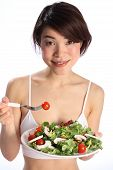 Smiling girl eating salad meal