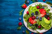 Mixed salad leaves with berries, avocado and honey-mustard dressing poster