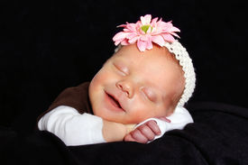 stock photo of newborn baby girl  - pretty baby girl sleeping with a big smile on her face - JPG