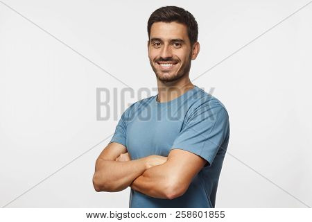 poster of Portrait Of Attractive Young Sporty Man In Blue T-shirt Standing With Crossed Arms Isolated On Gray
