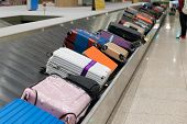 Suitcase Or Luggage With Conveyor Belt In The Airport. Traverler Waiting Suitcase Or Luggage In Arri poster