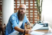 Bearded Stylish Writer With Cup Of Coffe Reading His Novel. Modern Writer In Glasses Working On New  poster