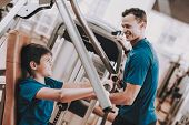 Young Father And Son Doing Exercises In Sport Club. Healthy Lifestyle Concept. Sport And Training Co poster