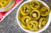 Slices of preserved Jalapeno pepper in bowl. poster