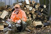 image of hunter  - deer hunter in blaze orange with a ten point whitetail trophy buck with a wood pile in the background - JPG