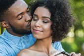 Handsome Man Kissing Tenderly His Beautiful Girlfriend In Cheek Outdoors poster