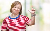 Young adult woman with down syndrome over isolated background showing and pointing up with fingers n poster