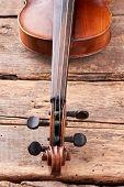 Old Violin Part On Wooden Planks Close Up. Scroll And Peg Box Of Violin Instrument. Details Of Desig poster