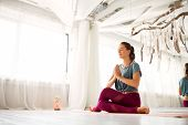 mindfulness, spirituality and healthy lifestyle concept - woman meditating at yoga studio poster