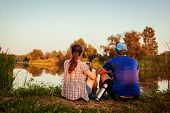 Young Couple Fishing And Drinking Tea On River At Sunset. People Relaxing And Chilling Outdoors poster