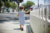 stock photo of girl walking away  - Little toddler girl in summer dress walking away along white fence - JPG