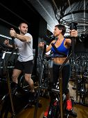 elliptical walker trainer man and woman at black gym training aerobics exercise