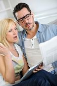 stock photo of horrifying  - Couple reading news with horrified look - JPG