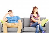 Sad young couple sitting on a sofa after an argument isolated on white background