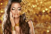 Fashion Beauty Girl Isolated On Golden Bokeh Lights Background. Glamour Makeup. Gold Jewelry. Hairst