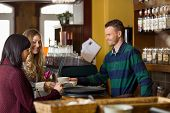 image of bartender  - Handsome bartender serving coffee to women at counter in cafe - JPG