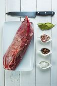 picture of shoulder-blade  - Raw veal meat and ingredients to cook it on the table of the kitchen - JPG