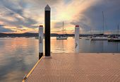 pic of pontoon boat  - Boats and yachts moored at sunset from New Brighton Public Wharf Saratoga NSW Australia - JPG