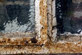 stock photo of putty  - rusty window frame with cracked glass and flaking putty - JPG