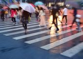 image of pedestrian crossing  - crowds of people crossing the street on a rainy day in the city  - JPG