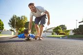 picture of skateboard  - young boy learning to ride skateboard as father teaches him in the suburb street having fun - JPG