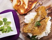 stock photo of lamb shanks  - Slow cooked lamb shanks served on wooden board with rice and gluten free naan bread