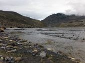 foto of mustang  - A Himalayan river flowing through the dry and bushy landscape of the Annapurna region of Mustang Nepal during monsoon - JPG