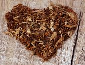 foto of tobacco leaf  - Dried tobacco leaves decorated in heart shape on wooden surface - JPG