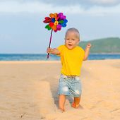 image of laughable  - Baby playing with toy windmill - JPG