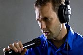 stock photo of singer  - male voice over artist or singer on a microphone wearing a blue shirt on a concrete background - JPG