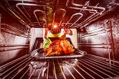 image of oven  - Housewife prepares roast chicken in the oven - JPG