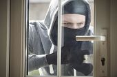 stock photo of social housing  - Burglar Breaking Into House By Forcing Door With Crowbar - JPG