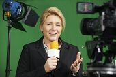 stock photo of presenter  - Female Journalist Presenting Report In Television Studio - JPG