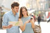 image of generic  - Couple of tourists consulting a city guide and smartphone gps in the street searching locations - JPG