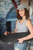 picture of coy  - A beautiful teen girl carrying her skateboard past a gray stone building - JPG
