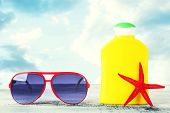 image of suntanning  - Bottle of suntan cream with sunglasses and sea star on table isolated on white - JPG