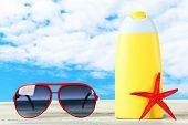 picture of suntanning  - Bottle of suntan cream with sunglasses and sea star on table isolated on white - JPG