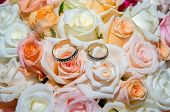 stock photo of wedding feast  - Wedding rings in a bouquet of roses - JPG