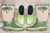 image of clog  - Stylish footwear for the garden with green rubber clogs and elegant matching green and beige gumboots in a symmetrical arrangement on a rustic wood background - JPG
