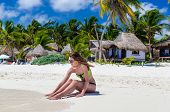 pic of beach hut  - Young cute woman in sunglasses and beautiful swimwear touching a sea wave and smiling in front of beach cabins on tropical white sandy beach during her Caribbean vacation in Tulum Mexico - JPG