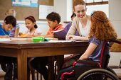 stock photo of redhead  - Teacher helping a disabled pupil at the elementary school - JPG