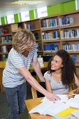 picture of classmates  - Student getting help from classmate in library at the university - JPG