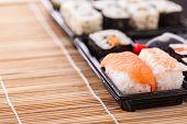 foto of sushi  - a sushi take away plastic tray box on a wooden bamboo sushi mat  - JPG