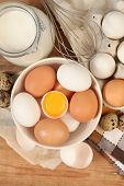 stock photo of chicken-wire  - Eggs and whisk on wooden table - JPG