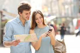 image of family planning  - Couple of tourists consulting a city guide and smartphone gps in the street searching locations - JPG